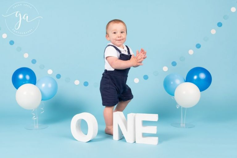 One year old at a cake smash with a blue background