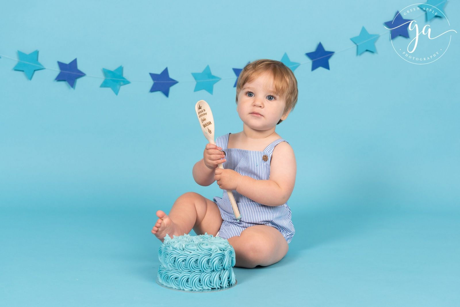 one year old boy on blue background holding wooden spoon