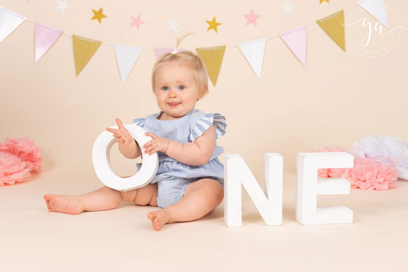 one year old girl holding one letters