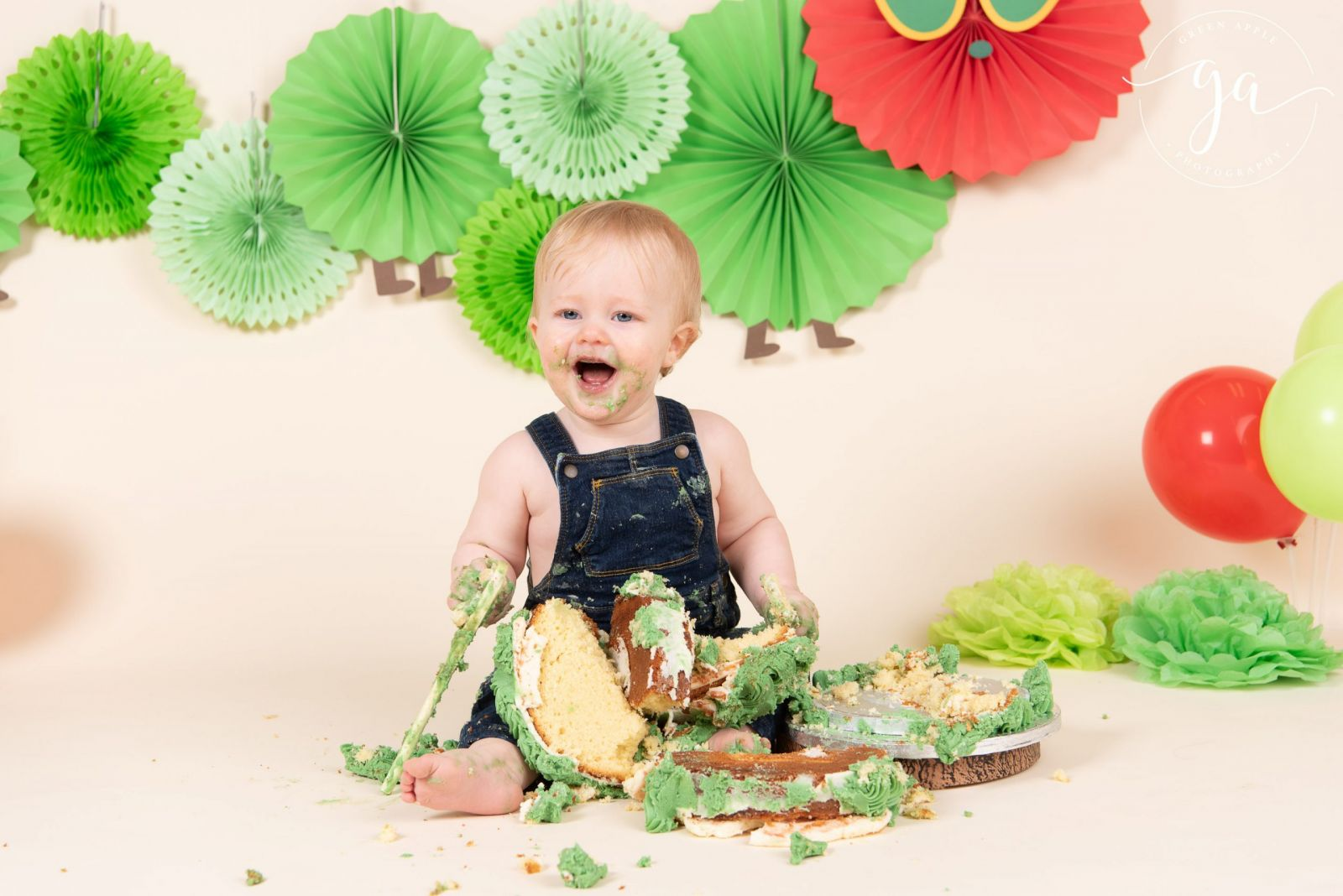 hungry caterpillar beige background baby cake smash toddler sitting in cake with spoon