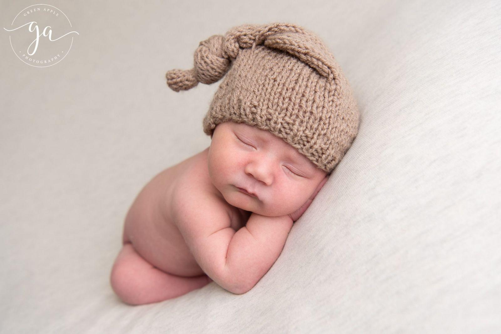 sleeping newborn boy with brown knitted hat